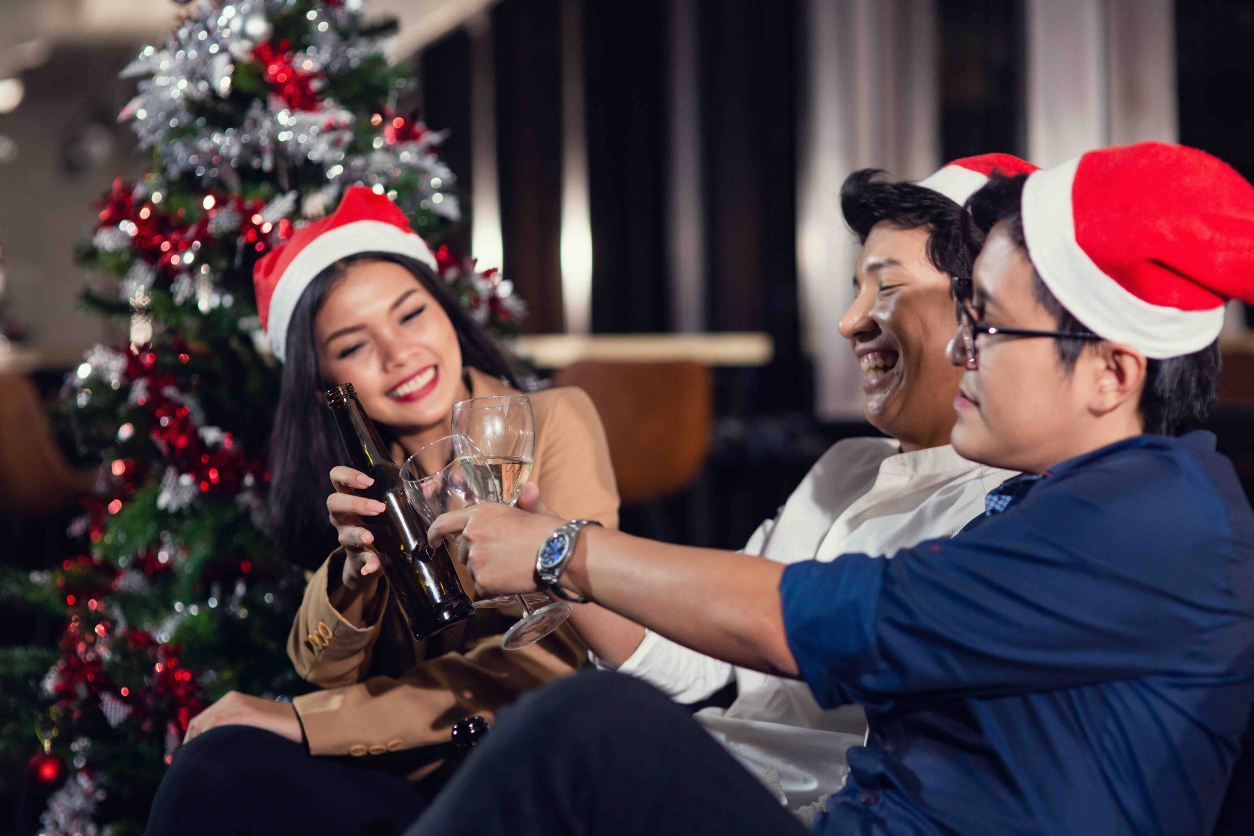 Group of multi generation drinking champagne and alcohol wareing santa hat. Group of various Multi nationalities friends having Christmas party together with happiness