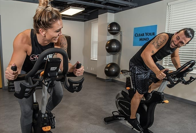 Man and Woman Using Spin Bikes in Resident Fitness Center