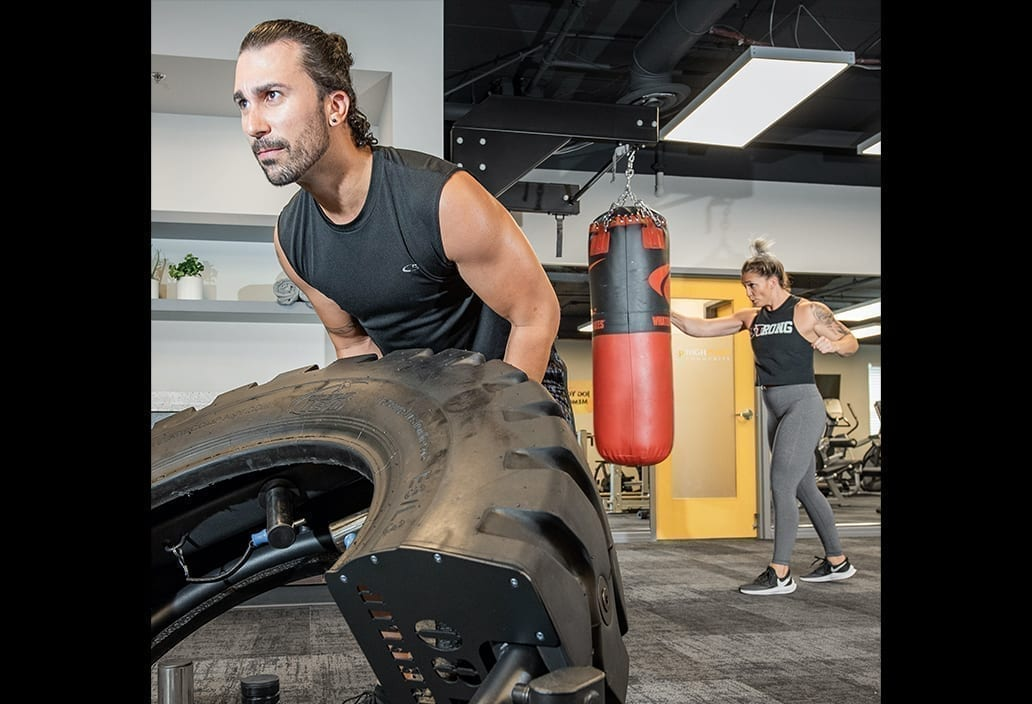 Man Flips tire and Woman Punches Punching Bag in Resident Fitness Center